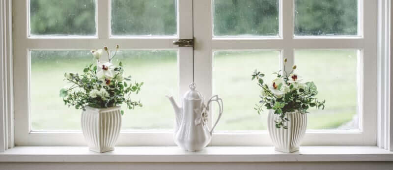 2 plants in white pots white coffee pot sitting on a white window sill by nathan fertig at unsplash